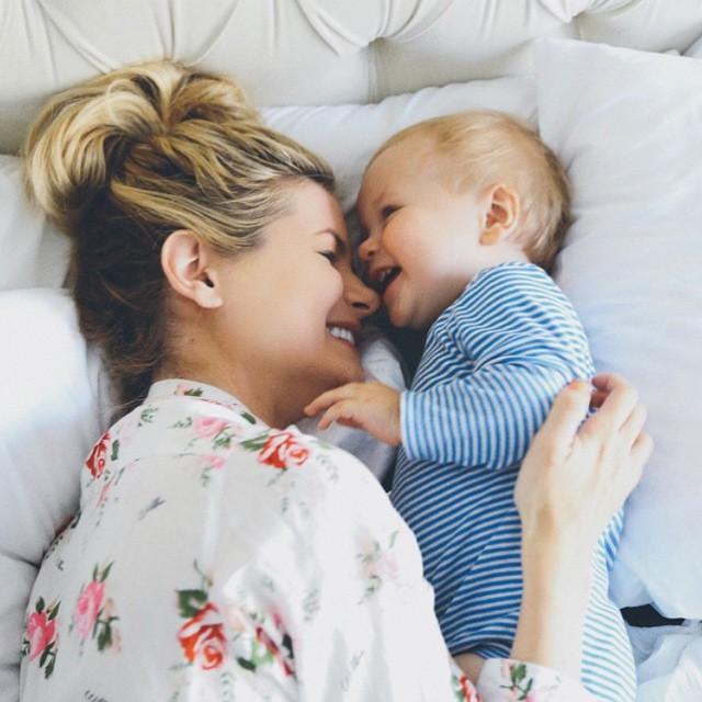 Mamá recostada en la cama junto a su bebé mientras están riendo