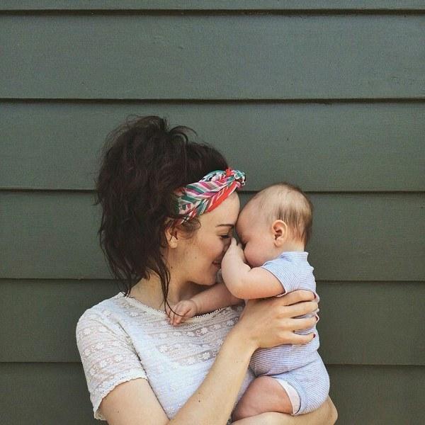 Chica sosteniendo a un bebé en brazos mientras besa su nariz
