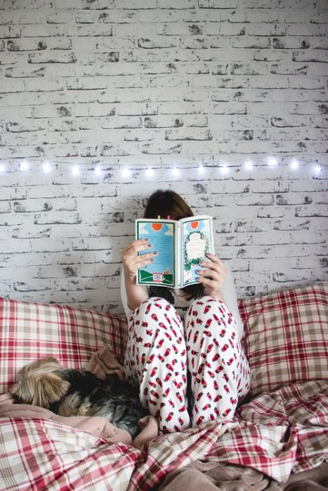 Chica en pijama leyendo un libro