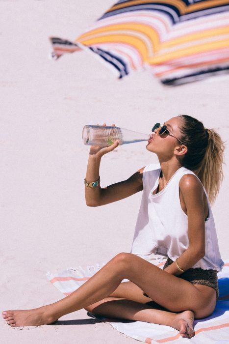 Chica en la playa bebiendo agua