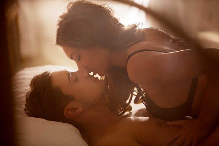 Pareja de novios recostados en la cama besándose