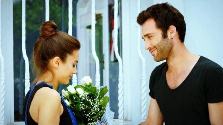 Chico entregándole flores a una chica