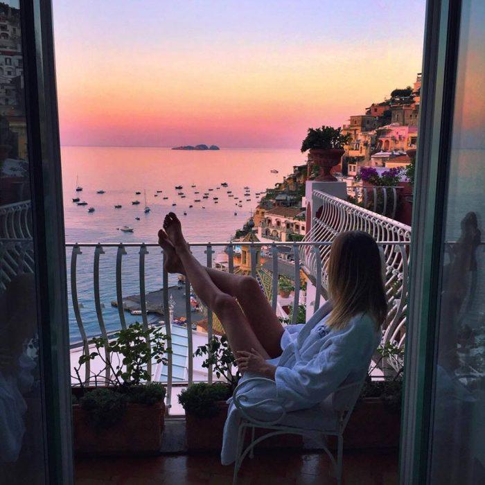 Chica sentada frente a un balcón viendo el atardecer