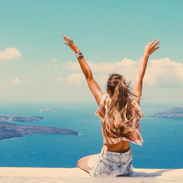 Chica con los brazos abiertos viendo hacia el horizonte
