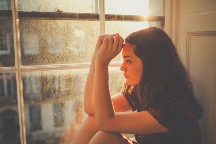 Chica sentada frente a una ventana pensando