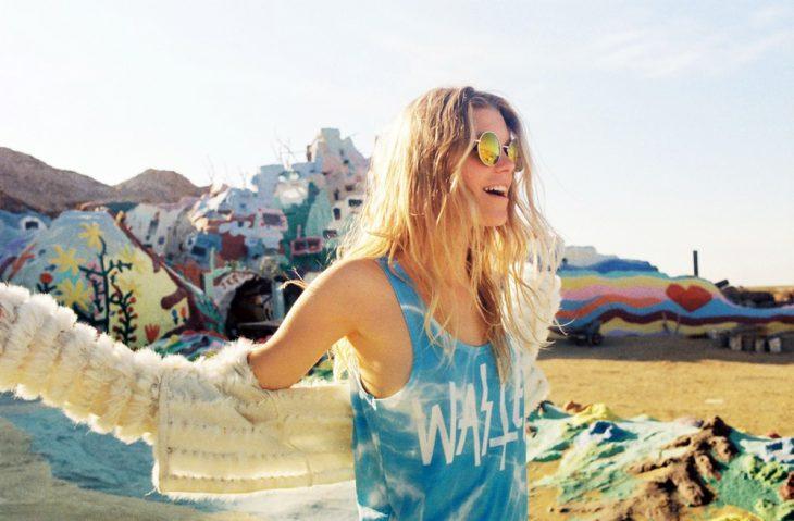Chica sonriendo mientras viste una camisa azul y suéter color arena