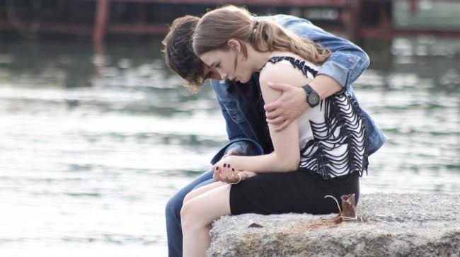 Chico abrazando a una chica mientras ambos están sentados en un muelle