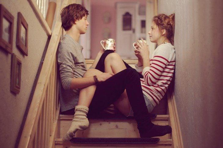 Chicos sentados en una escalera tomando café