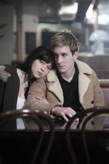 Chica sentada junto a un chico en una cafetería mientras están abrazados