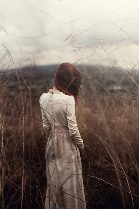 Chica parada en un campo de hierva