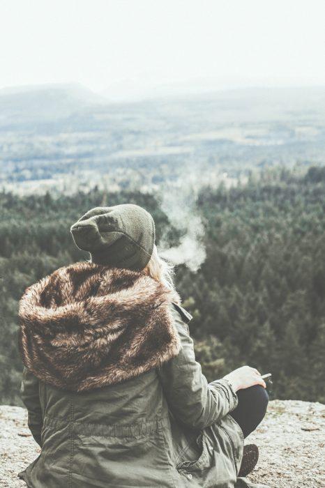 Chica fumando en una montaña