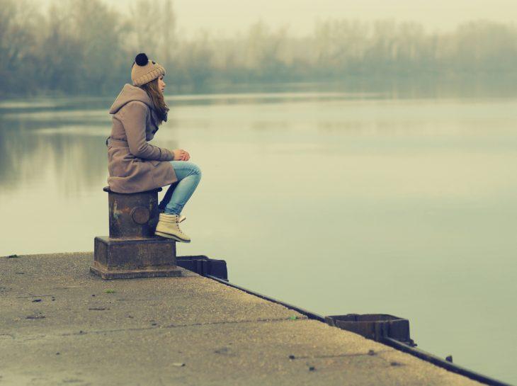 Chica pensando sentada a la orilla de un lago