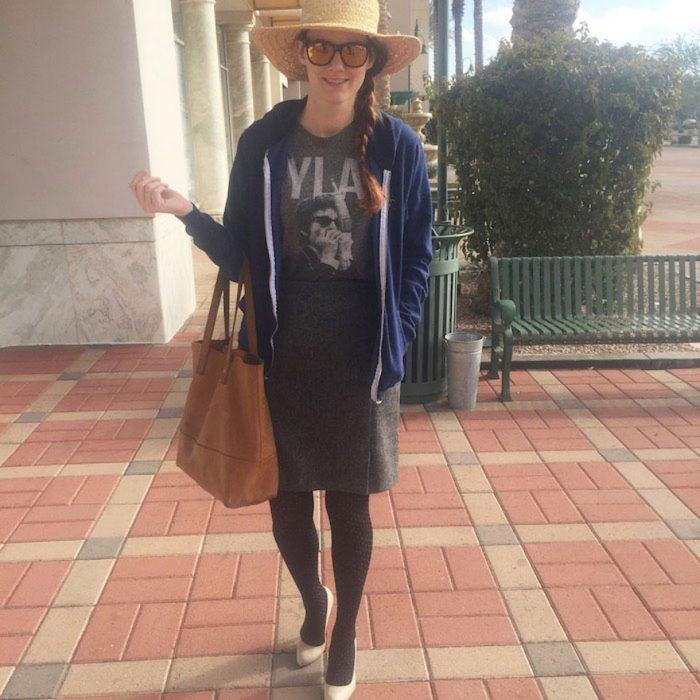 Chica usando una falda y camisa gris un sombrero, lentes y zapatos de tacón