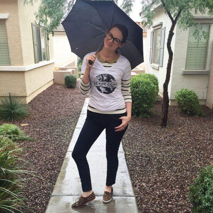 Chica sosteniendo una sombrilla mientras está parada bajo la lluvia posando para una foto