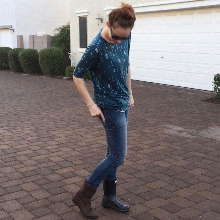 Chica usando un par de botas distintas, jeans y camisa de flechas