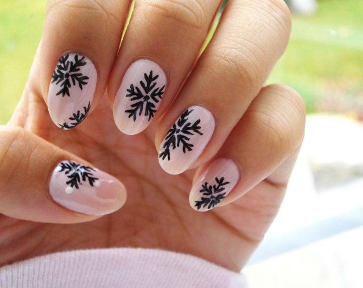Diseño de uñas navideñas pintadas en color rosa con copos de nieve color negro