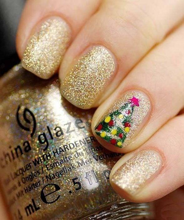 Diseño de uñas navideñas en color dorado con un pino verde