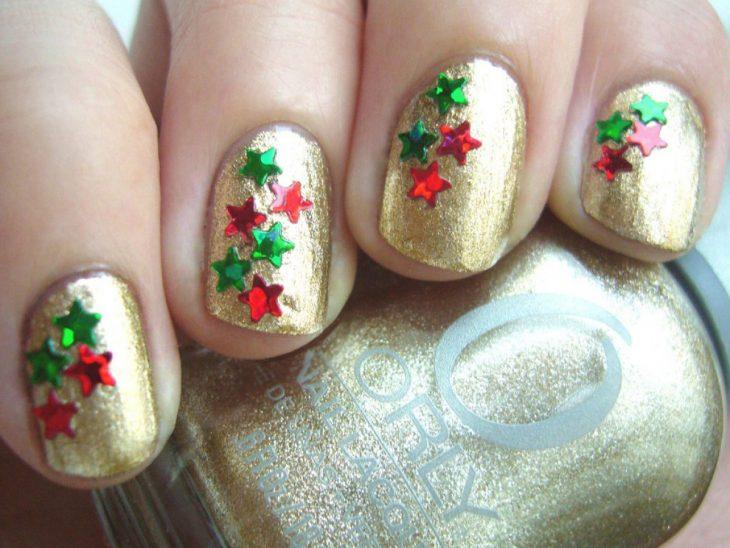 Diseño de uñas navideño, uñas decoradas con esmalte dorado y estrellas