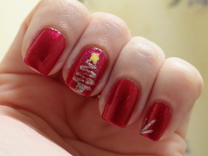 Decoración de uñas en color rojo con un pino en color plateado