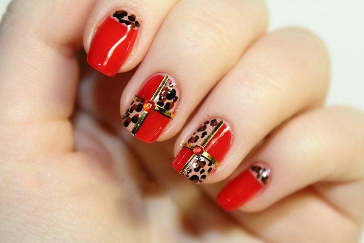 Diseño de uñas navideño, decoradas en color rojo como un regalo