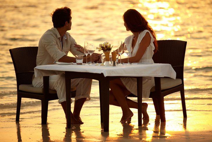 Pareja teniendo una cena romántica a la orilla del mar