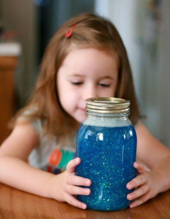 niña con un frasco con brillantina