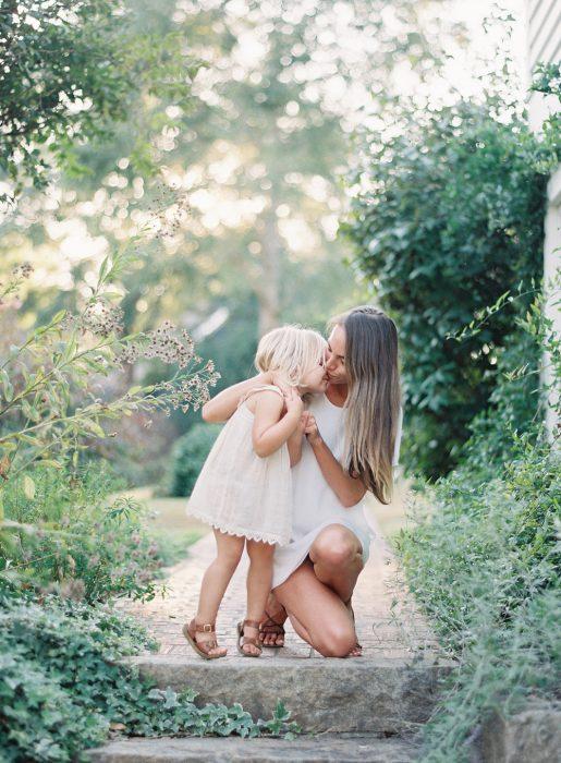 Madre besando a su hija en la mejilla