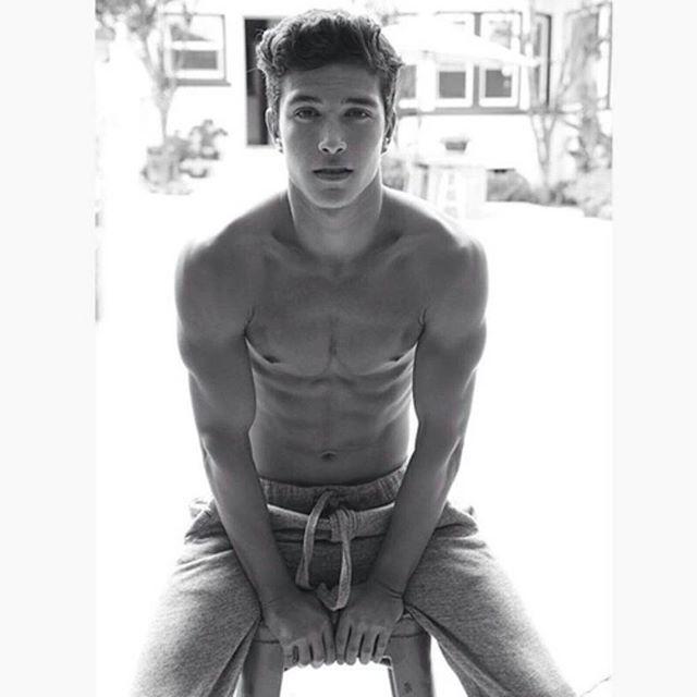 Chico sentado en un banco en pants y sin camisa