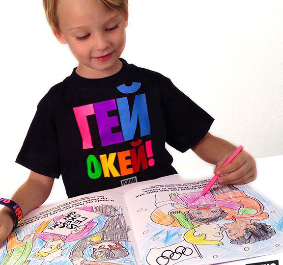 Niño sosteniendo un libro para colorear donde hay dibujos de parejas del mismo sexo