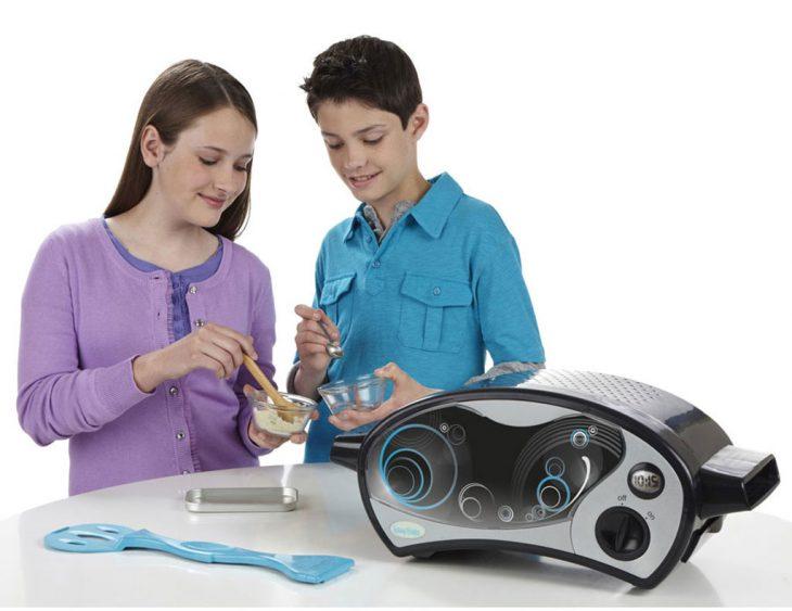 Niña y niño jugando con un micro hornito para cocinar pasteles
