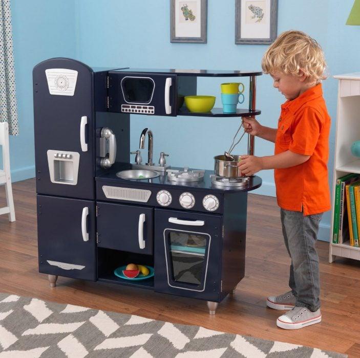 Niño jugando en una cocina de juguete