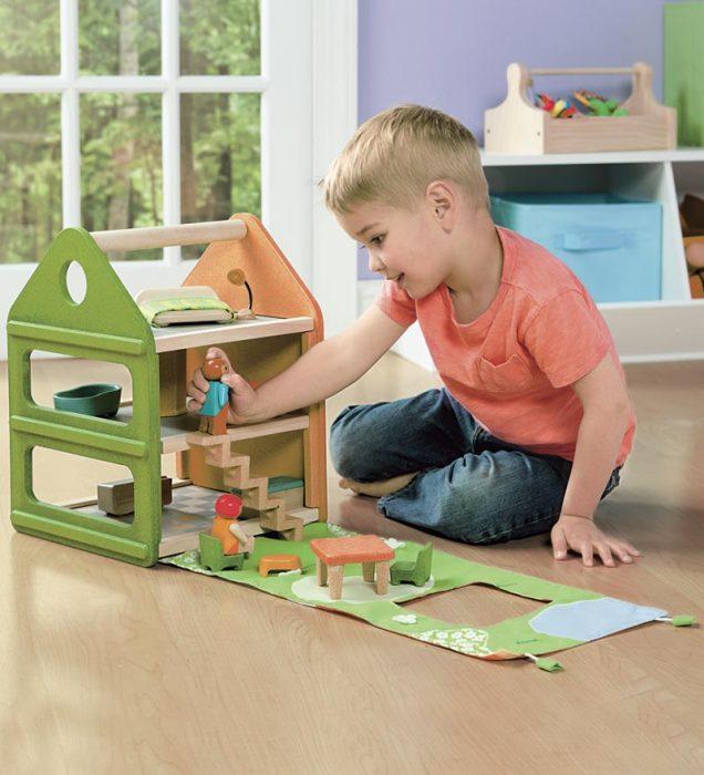 Niño jugando con una casa de muñecas
