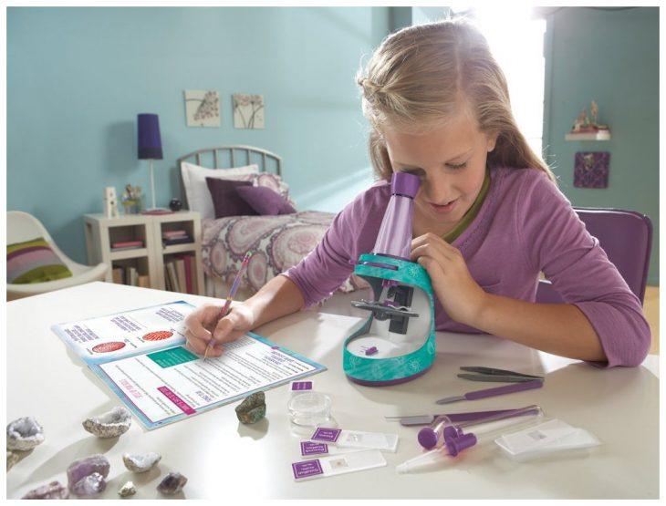 Niña jugando con un microscopio de juguete
