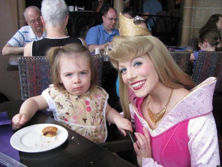 Niña molesta por que no la dejan comer mientras esta junto a una princesa