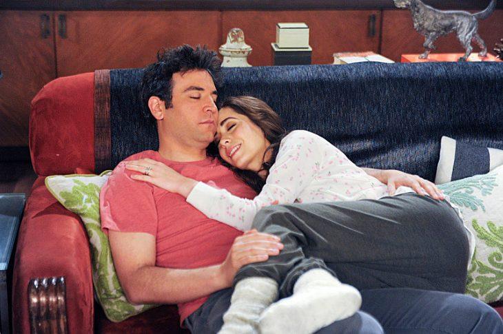 pareja acurrucados en un sofá