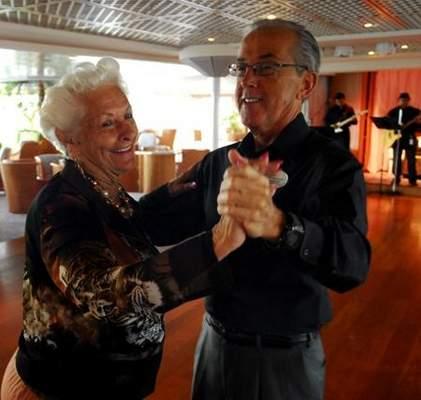 Mujer de 87 años que vive en un crucero bailando con una persona de la tripulación