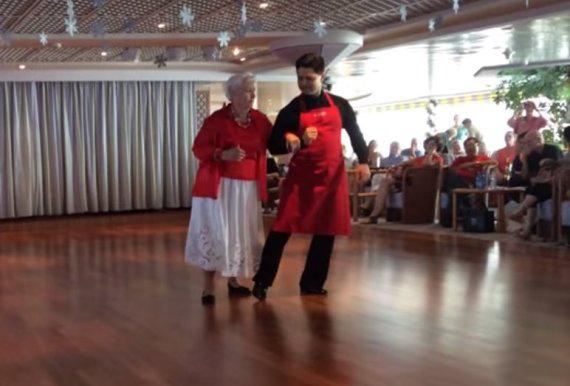 Mujer de 87 años que vive en un crucero bailando con un mesero
