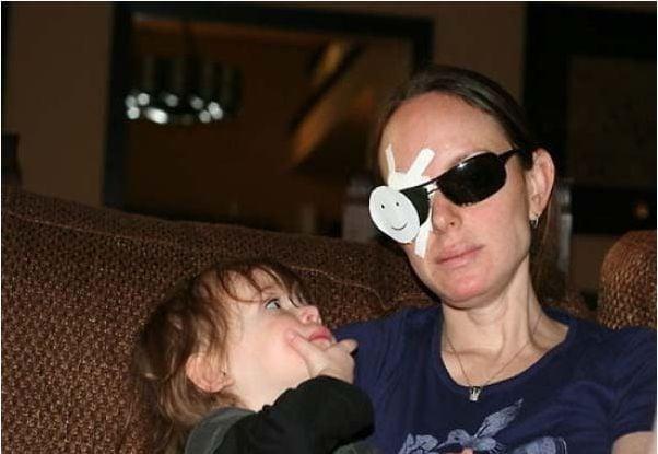 Mamá sosteniendo a su hijo con un parche en el ojo