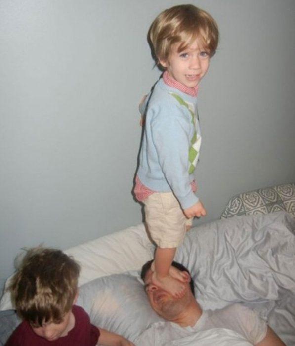 Niño parado sobre la cara de su padre