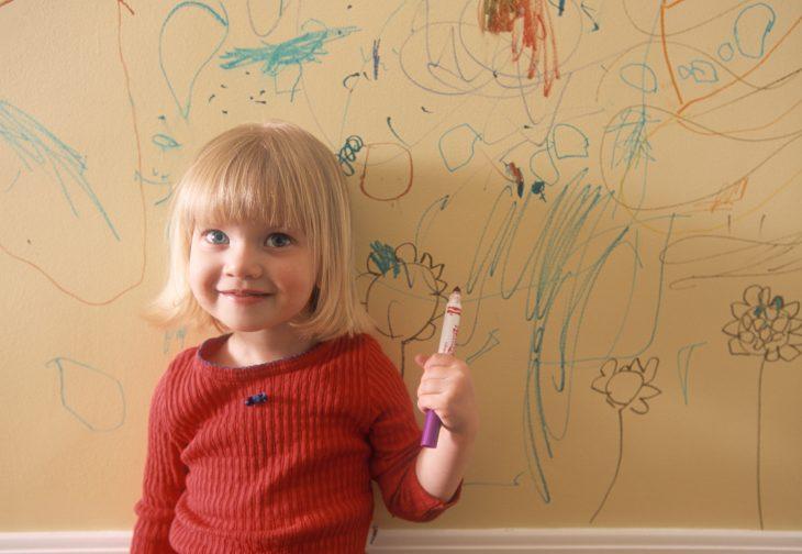 Niña dibujando en las paredes de su casa