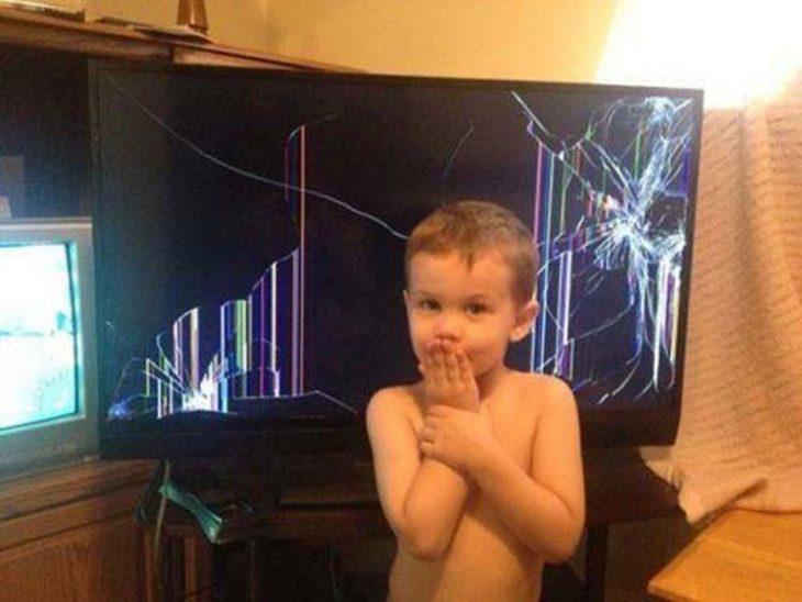 Niño tapandose la boca después de haber destruido la televisión