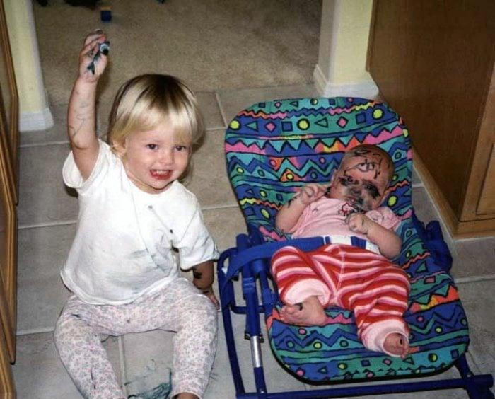 niño con un plumón pintando la cara de su hermana
