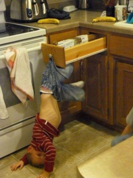 Niño colgando de sus pantalones desde un cajón