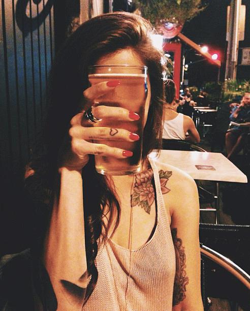 Chica sosteniendo una cerveza en las manos