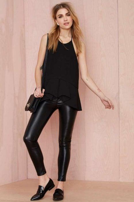 Chica parada en sobre una pared usando ropa negra y unas flats del mismo color