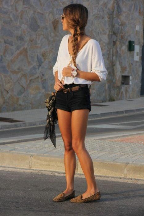 Chica usando unos zapatos flats mientras está parada en la calle