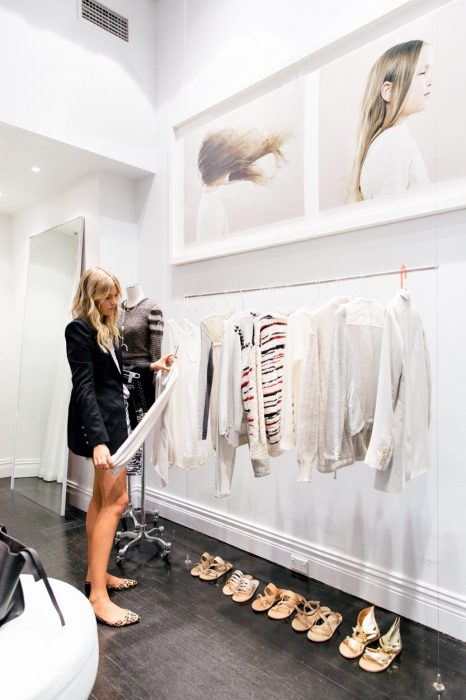 Chica eligiendo ropa de un perchero
