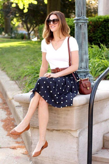 Chica sentada sobre unas escaleras usando una falda azul con puntos y una blusa blanca y flats color café