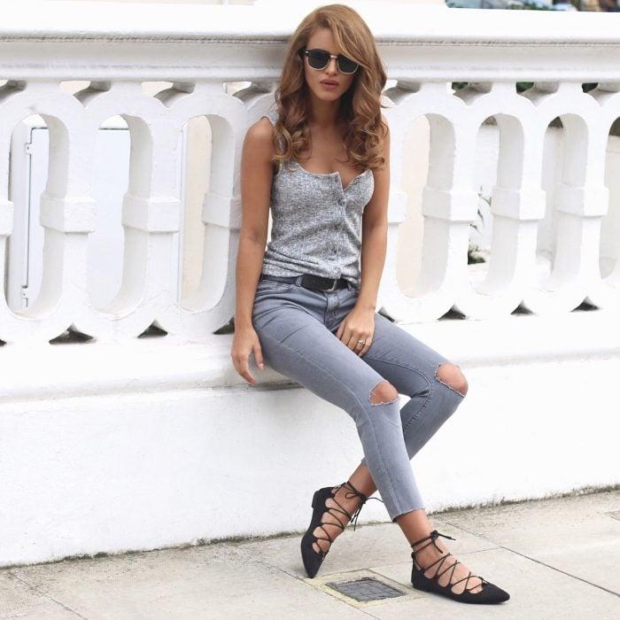Chica sentada frente a una pared usando unos zapatos flats