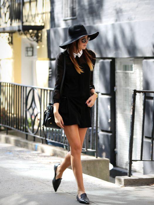Chica caminando por la calle usando falta blusa sombrero y zapatos flats